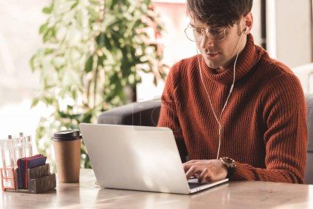 Photo pour Beau jeune homme écoutant de la musique dans les écouteurs et en utilisant un ordinateur portable près de tasse en papier dans le café - image libre de droit
