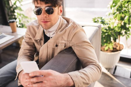 Photo for Selective focus of trendy man in sunglasses using smartphone in cafe - Royalty Free Image