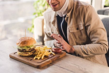 Photo for Cropped view of cheerful man looking at tasty burger and french fries on cutting board in cafe - Royalty Free Image