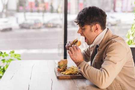 Photo for Handsome man eating tasty burger in cafe - Royalty Free Image