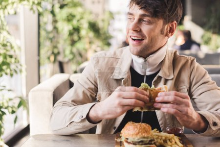 Photo for Selective focus of happy young man holding tasty burger near french fries on cutting board in cafe - Royalty Free Image