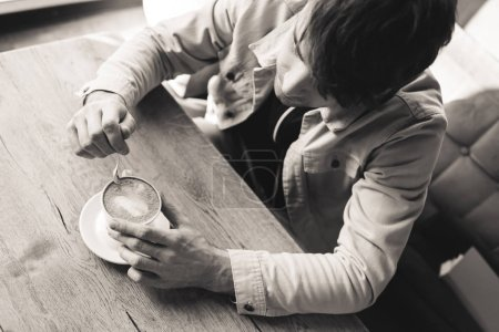 Photo for Overhead view of man holding spoon near cup with cappuccino in cafe, black and white photography - Royalty Free Image