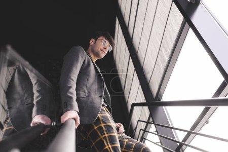 Photo pour Heureux homme élégant dans des verres debout dans les escaliers - image libre de droit