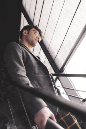 Photo pour Jeune homme élégant dans des verres debout dans les escaliers - image libre de droit