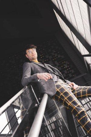 Photo pour Jeune homme élégant dans des lunettes posant sur les escaliers et regardant la caméra - image libre de droit