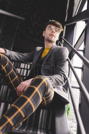 cher homme élégant dans des lunettes assis sur les escaliers près des fenêtres