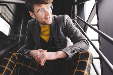 smiling stylish man in glasses sitting on stairs near windows