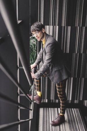 Photo pour Tendance jeune homme dans des verres debout dans les escaliers - image libre de droit
