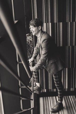 Photo pour Tendance jeune homme lunettes de soleil souriant en se tenant debout sur la photographie de l'escalier, noir et blanc - image libre de droit