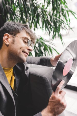 cheerful young man in sunglasses holding vinyl record in hands