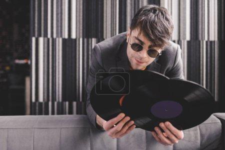 Photo pour Élégant jeune homme lunettes de soleil tenant des disques vinyles rétro - image libre de droit