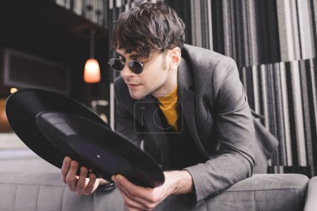 Photo for Stylish young man in sunglasses looking at retro vinyl records - Royalty Free Image