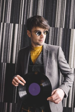 Photo pour Beau jeune homme à lunettes de soleil tenant le disque vinyle rétro en plastique - image libre de droit