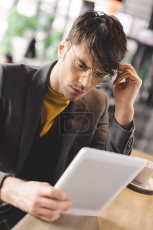 thoughtful young man in glasses sitting at bar counter while looking at digital tablet near cup with coffee