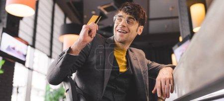 Photo pour Homme heureux dans des verres assis au comptoir, tout en maintenant la carte de crédit en café - image libre de droit