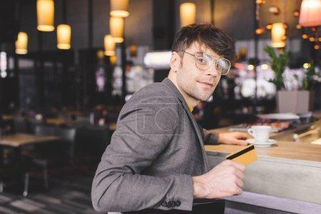 Foto de Enfoque selectivo del hombre gafas sentado en barra contraria mientras sostiene la tarjeta de crédito en la cafetería - Imagen libre de derechos