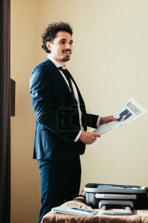 Foto de Empresario sosteniendo periódico de negocios junto a la cama con el equipaje en la habitación de hotel - Imagen libre de derechos