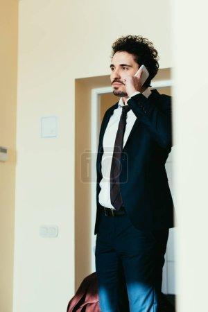 Foto de Hombre de negocios en traje hablando por teléfono inteligente durante el viaje de negocios en la habitación de hotel - Imagen libre de derechos