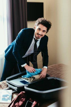 Foto de Sonriente hombre de negocios con la ropa en bolsa de viaje en cama en habitación de hotel - Imagen libre de derechos