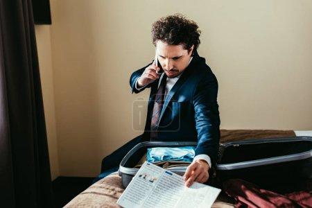 Photo pour Homme d'affaires parler sur smartphone et tenant le journal tout en étant assis sur le lit avec la valise dans la chambre d'hôtel - image libre de droit