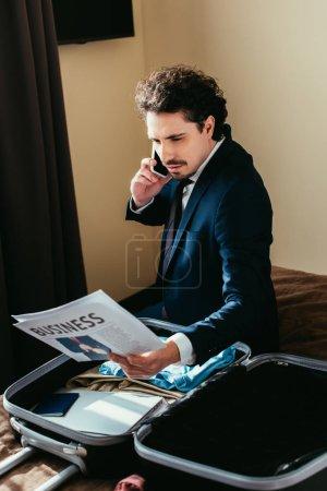 Photo pour Homme d'affaires parler sur smartphone et regarder le journal d'affaires tout en étant assis sur le lit avec la valise dans la chambre d'hôtel - image libre de droit