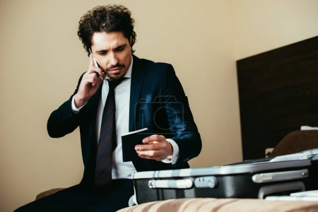 Photo for Handsome businessman talking on smartphone and holding passport while sitting on bed with luggage in hotel room - Royalty Free Image