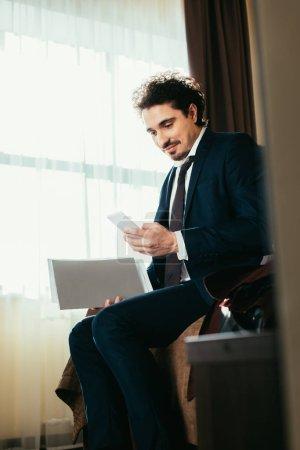 Photo pour Homme d'affaires en costume tenant des documents et utilisant un smartphone dans la chambre d'hôtel - image libre de droit