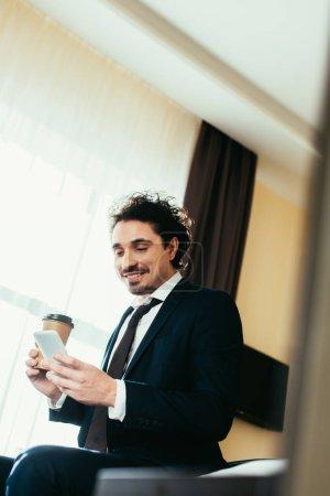Foto de Empresario sonriente con smartphone y celebración de café en habitación - Imagen libre de derechos