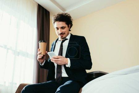 Foto de Hombre de negocios feliz con el teléfono inteligente y la celebración de la taza de café desechable en la habitación de hotel - Imagen libre de derechos