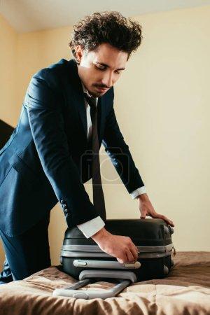 Photo pour Homme d'affaires professionnel en costume avec la valise sur le lit dans la chambre d'hôtel - image libre de droit