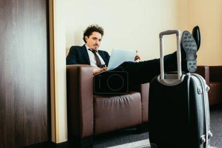 Photo pour Homme d'affaires télétravail sur ordinateur portable avec les jambes sur le sac de voyage en chambre d'hôtel - image libre de droit
