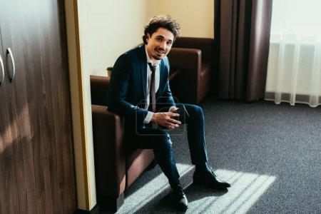 Photo pour Homme d'affaires heureux détenteurs d'un passeport et assis dans une chambre d'hôtel - image libre de droit
