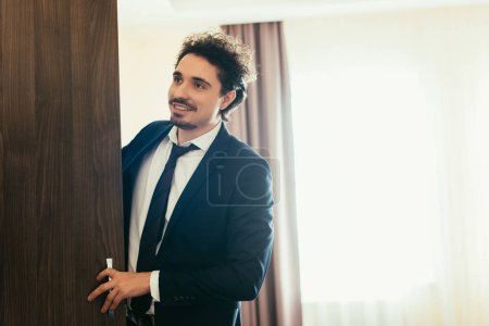 Photo for Handsome smiling businessman opening wardrobe in hotel room - Royalty Free Image