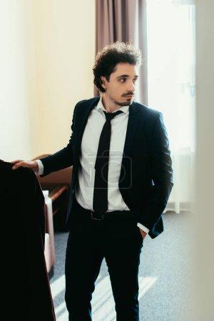 Photo pour Bel homme d'affaires détenant des vêtements dans la chambre d'hôtel - image libre de droit