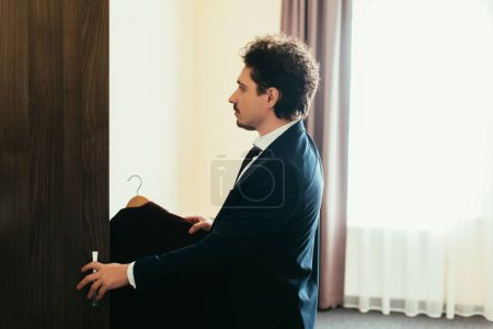 Photo for Businessman in suit taking clothes from wardrobe in hotel room - Royalty Free Image