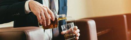 Photo pour Vue recadrée d'homme d'affaires, verser le whisky de bouteille en verre dans la chambre d'hôtel - image libre de droit