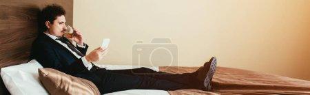 Photo pour Homme d'affaires en costume à l'aide de smartphone et whisky à boire à un lit dans une chambre d'hôtel - image libre de droit
