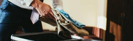 Photo pour Vue recadrée de l'homme d'affaires mettant des vêtements dans un sac de voyage - image libre de droit
