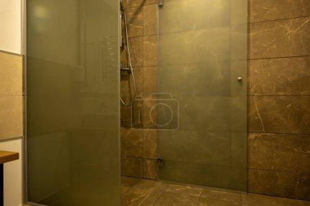 Foto de Interior del cuarto de baño con cabina de ducha de vidrio y azulejo marrón - Imagen libre de derechos