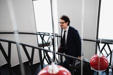 Photo pour Homme d'affaires souriant avec valise en remontant dans les escaliers dans l'hôtel - image libre de droit