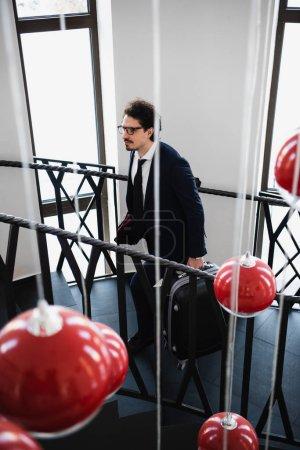 Photo pour Mise au point sélective des lampes rouges et homme d'affaires avec valise en remontant dans les escaliers dans l'hôtel - image libre de droit