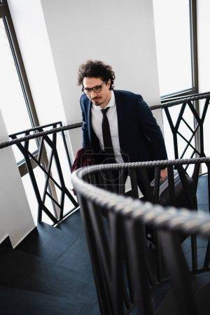 Photo pour Mise au point sélective d'homme d'affaires avec valise en remontant dans les escaliers dans l'hôtel - image libre de droit