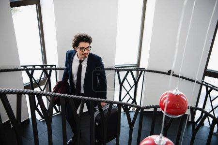 Photo pour Homme d'affaires en costume avec valise en remontant dans les escaliers dans l'hôtel - image libre de droit