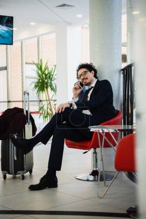 Photo pour Homme d'affaires souriant talking sur smartphone en attendant dans le hall de l'hôtel avec sac de voyage - image libre de droit