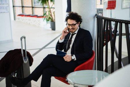 Photo pour Homme d'affaires souriant talking sur smartphone et en regardant de passeport en attendant dans le hall de l'hôtel avec valise - image libre de droit
