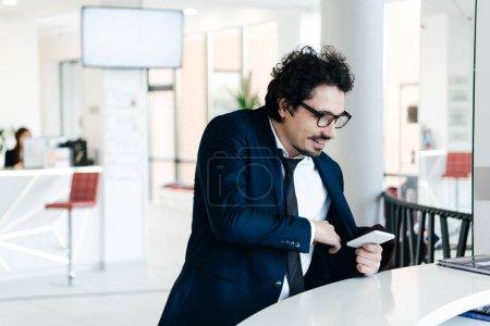 Photo pour Homme d'affaires avec un smartphone qui à réception pour le check-in à l'hôtel - image libre de droit