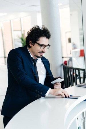 Photo pour Bel homme d'affaires souriant avec le smartphone, passeport une check-in à l'hôtel - image libre de droit