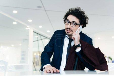 Photo pour Bel homme d'affaires avec passeport parler sur smartphone en faisant check-in à l'hôtel - image libre de droit
