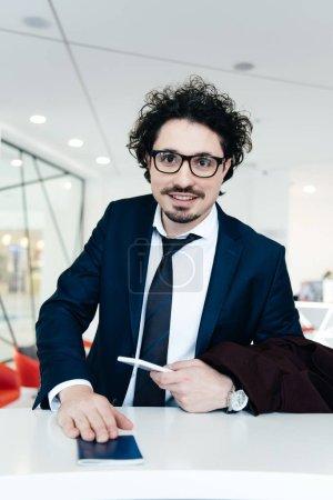 Photo pour Homme d'affaires souriant avec le smartphone, passeport une check-in à l'hôtel - image libre de droit