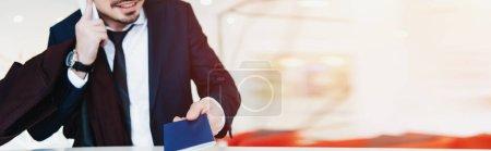Photo pour Recadrée vue d'homme d'affaires avec passeport parler sur smartphone en faisant check-in à l'hôtel - image libre de droit
